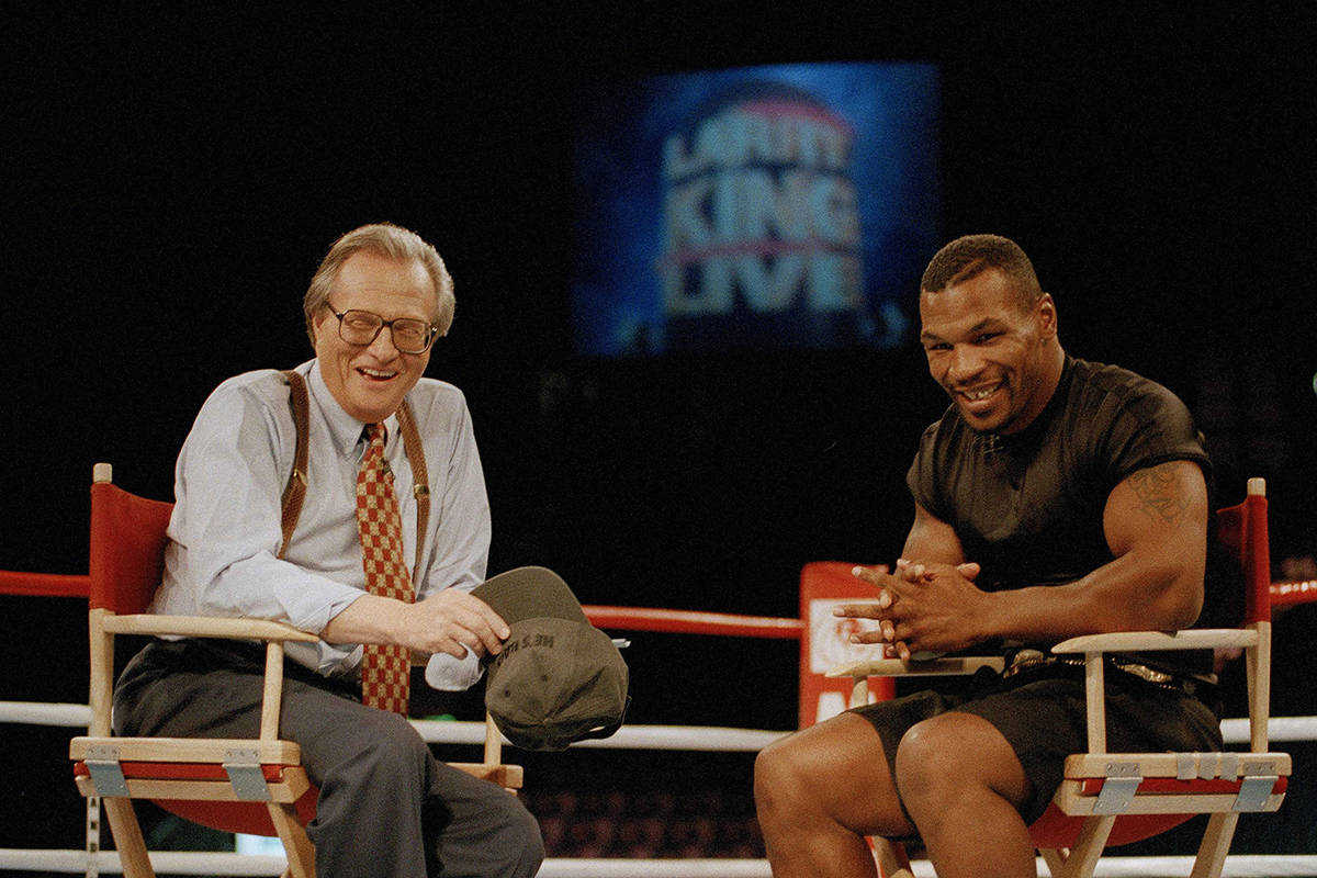 """FILE - In this Aug. 16, 1995 file photo, former heavyweight champion Mike Tyson, right, shares a laugh with TV talk show host Larry King during the broadcasting of the """"Larry King Live"""" show from inside the ring at the MGM Grand Gardens in Las Vegas. King, who interviewed presidents, movie stars and ordinary Joes during a half-century in broadcasting, has died at age 87. Ora Media, the studio and network he co-founded, tweeted that King died Saturday, Jan. 23, 2021 morning at Cedars-Sinai Medical Center in Los Angeles. (AP Photo/Lennox McLendon, File)"""